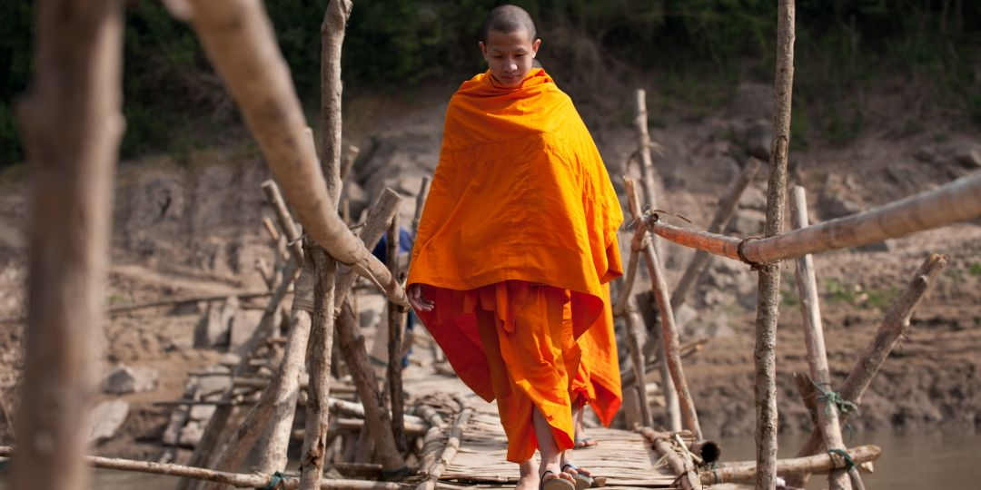 An apprentice monk crossing the bridge to Luang Prabang