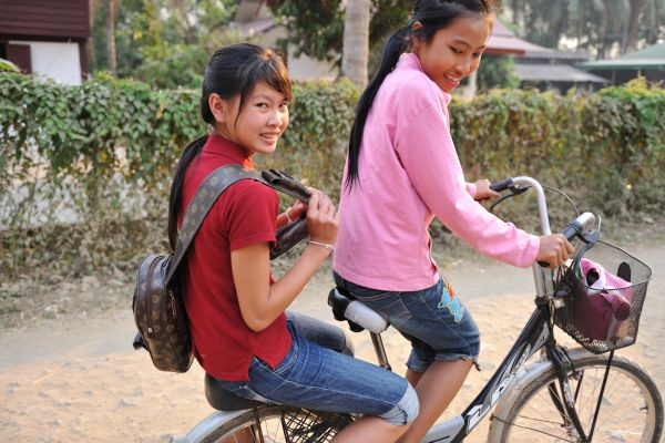 Por and Leh riding a bicycle near their home.
